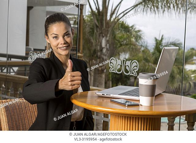 Trendy young woman holding thumb up and smiling at camera sitting at table with laptop and coffee in resort cafe
