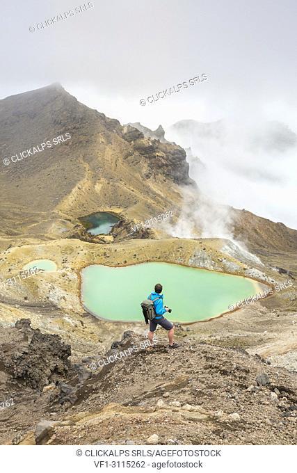 Man taking photos of Emerald Lakes. Tongariro Alpine Crossing, Tongariro NP, Waikato region, North Island, New Zealand