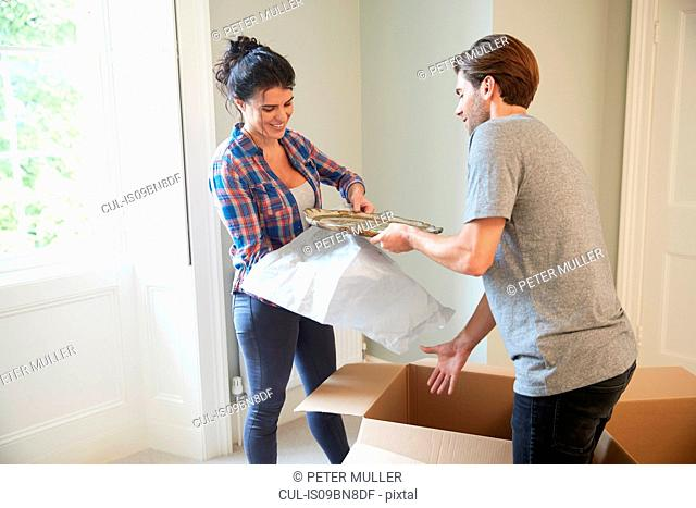 Couple packing belongings into cardboard box