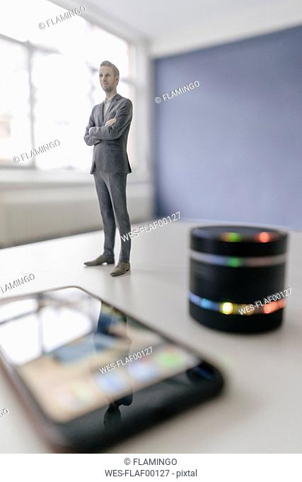 Miniature businessman figurine standing next to smart home loudspeaker and smartphone