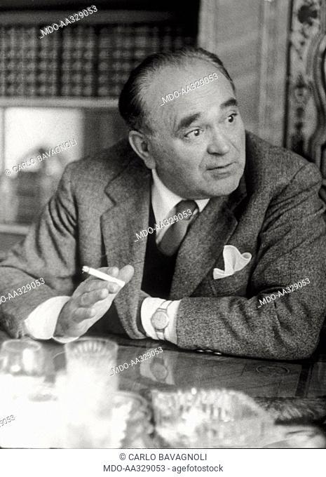 Bruno Baiocchi. Bruno Baiocchi, financial backer of the new television company, talks while smoking a cigarette