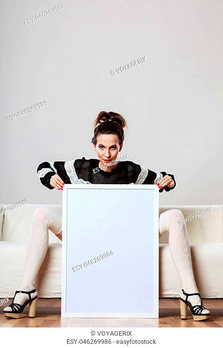 Advertisement concept. Fashionable woman sitting on sofa with blank presentation board. Female model showing banner sign billboard copy space for text