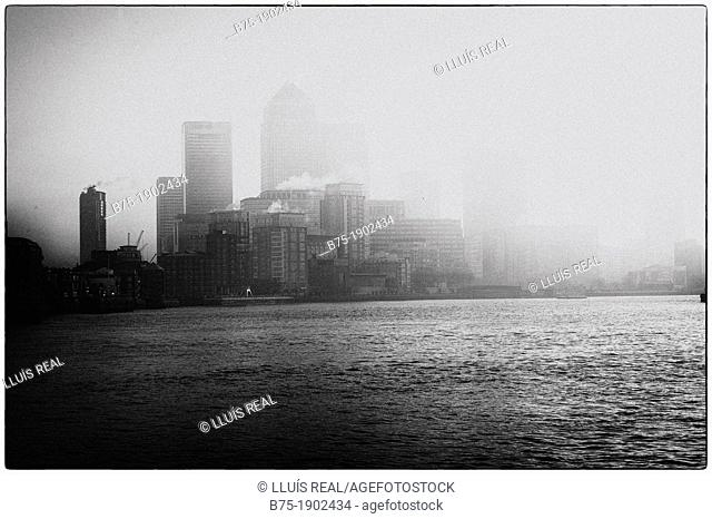 Canary Wharf, seen from the river Thames with fog, London, England, UK