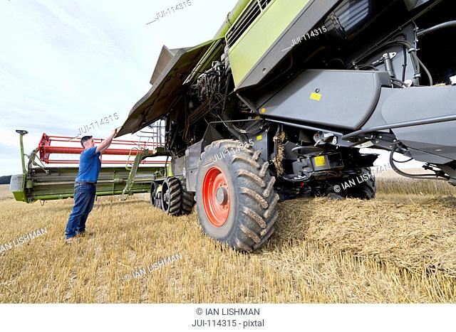 Combine Harvester Being Repaired In Field During Harvest