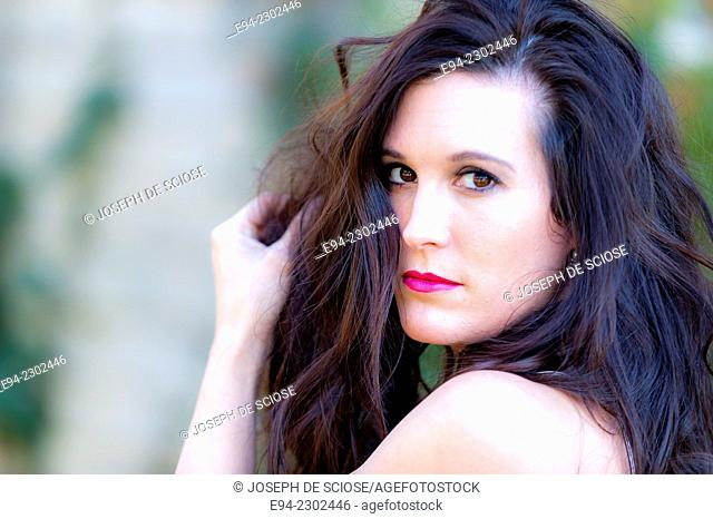 36 year old brunette woman outdoors looking over her shoulder directly at the camera