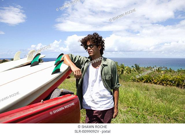 Young man leaning against surfboard in car, portrait