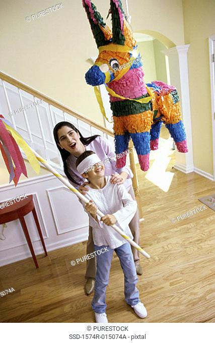 High angle view of a mother helping her daughter hit a pinata