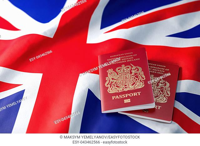 UK passport on the flag of the United Kingdom. Getting a UK passport, naturalization and immigration concept. 3d illustration