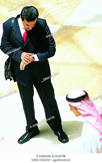 Arab businessman looking at his wristwatch