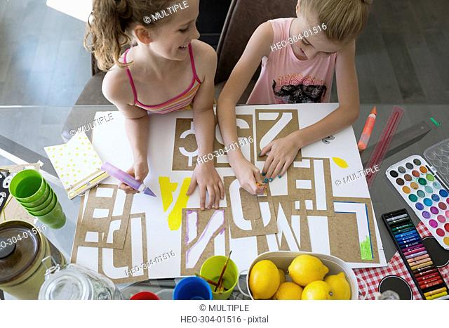 Girls making lemonade sign with stencils at dining table