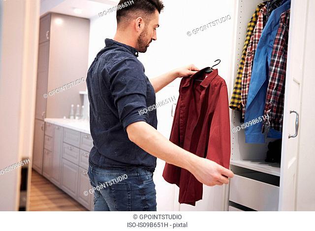 Man choosing shirt from closet