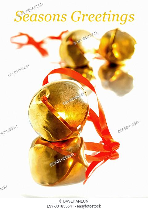 Golden sleigh bells with red ribbon,. Festive christmas card concept