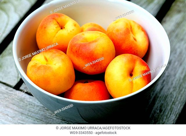 Apricots in a white bowl on a wooden table