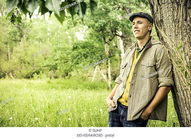 Young man wearing flat cap leaning against tree looking away smiling