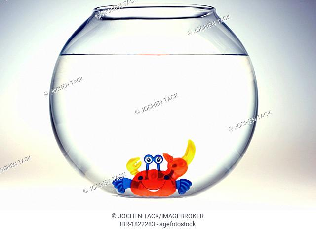 Wind-up toy crab with a friendly grin in a fish bowl, illustration