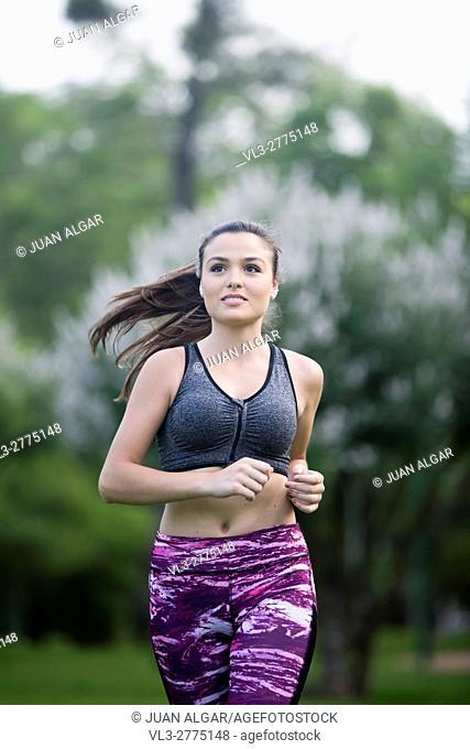 Portrait of beautiful sportswoman smiling away while running in park. Bokeh