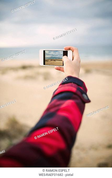 Woman's hand taking picture of the beach with smartphone