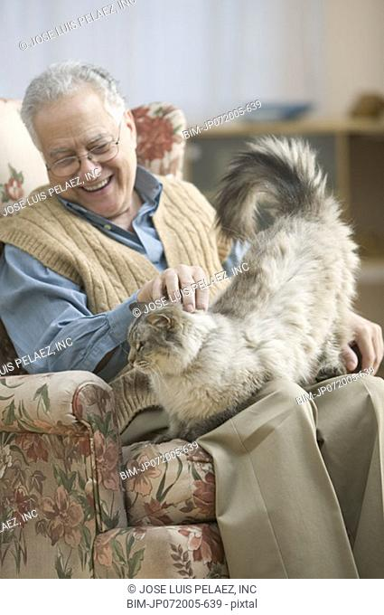 Older man in an arm chair petting his cat