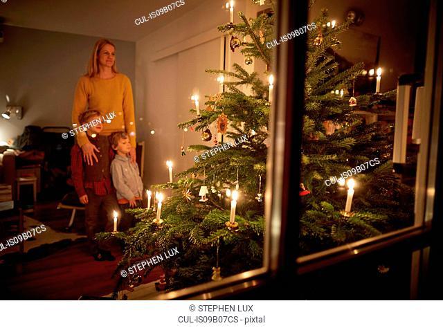 Mother and sons sitting at home at Christmas, looking at illuminated Christmas tree