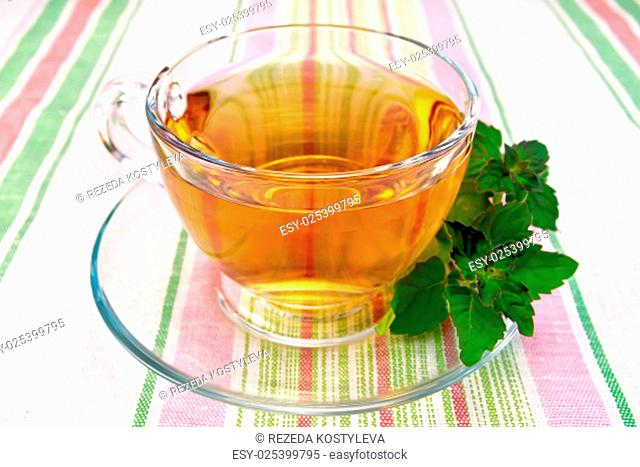 Herbal tea in a glass cup, fresh mint leaves on a background of striped linen tablecloths
