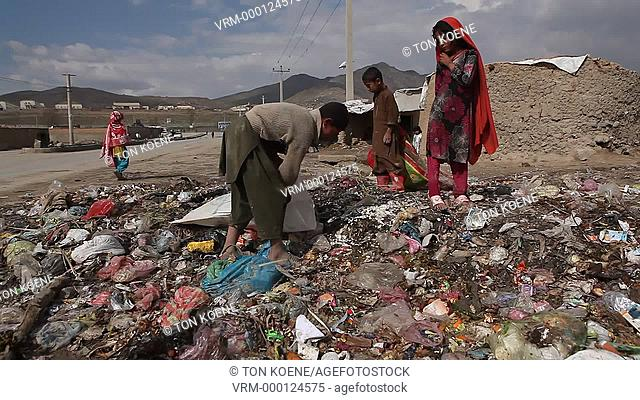 poor Afghan childrenm collecting rubbish to cook on and heating
