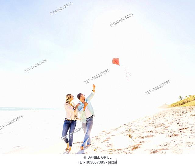 Couple on beach with kite
