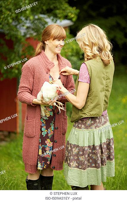 Two women in field holding hen