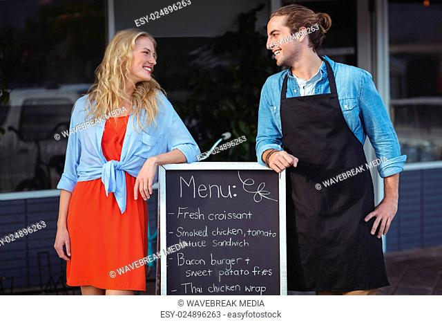 Waiter and woman standing with menu board outside the cafe