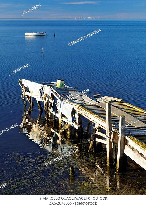 Pallets pier, fishing boat and Sea Salt heap at Alfacs Bay. Ebro River Delta Natural Park, Tarragona province, Catalonia, Spain