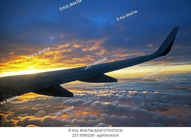 The wing of a plane flying above the clouds over a spectacular sunset at 10000 meters