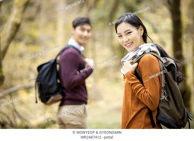 Side view portrait of young female trekker with a male trekker in forest