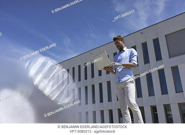 Business man using laptop while in front of modern house. Germany, Bavaria