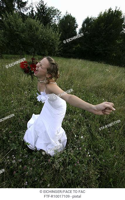 Bride with bouquet yelling outdoors, elevated view