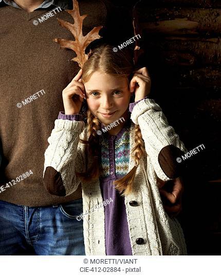 Girl using leaves as antlers
