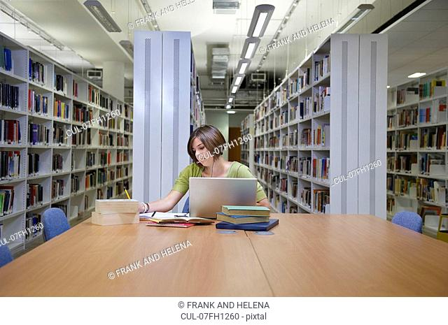 Young multitasking student in library