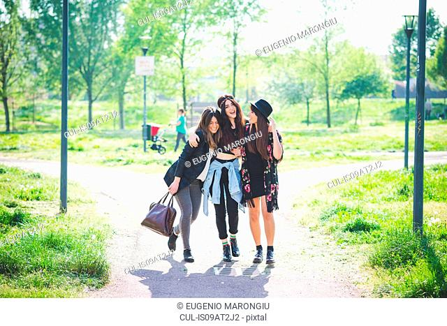 Three young female friends strolling together in park