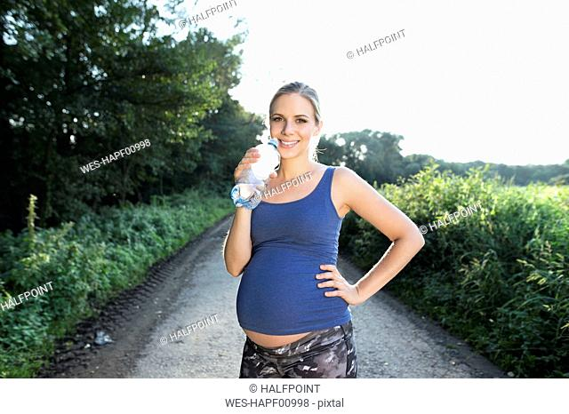 Pregnant woman taking a break from jogging drinking water from bottle