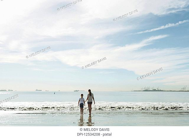 Two sisters walking out to the surf on a beach; Long Beach, California, United States of America
