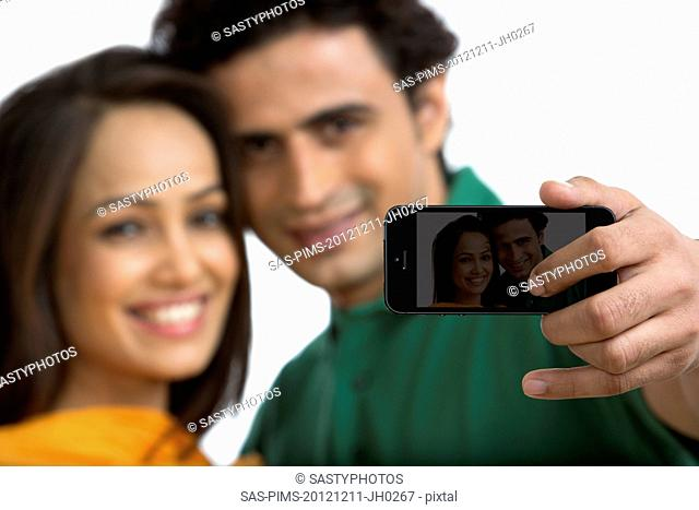 Couple taking a picture of themselves with a mobile phone