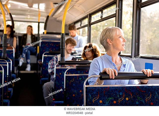 Female commuter looking through window while travelling in bus