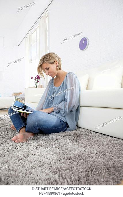 Young woman reading in her living room