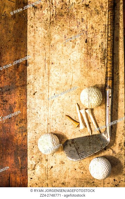 Still-life golfing picture of a single golf club beside three balls and four tees on grimy wood background