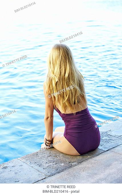 Caucasian woman sitting at the edge of swimming pool