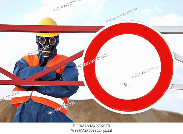 Germany, Man in protective workwear near stop sign