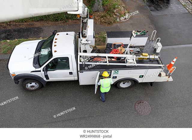 High angle view of cable lineman at bucket truck