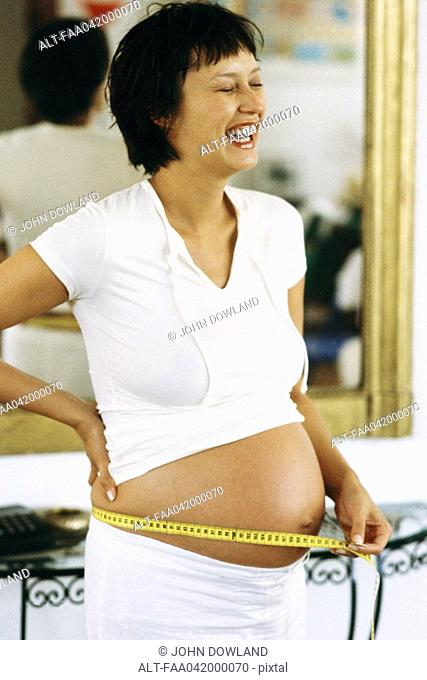 Pregnant woman measuring stomach with measuring tape, laughing