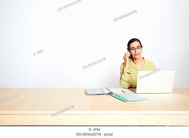 Woman at desk using phone and laptop