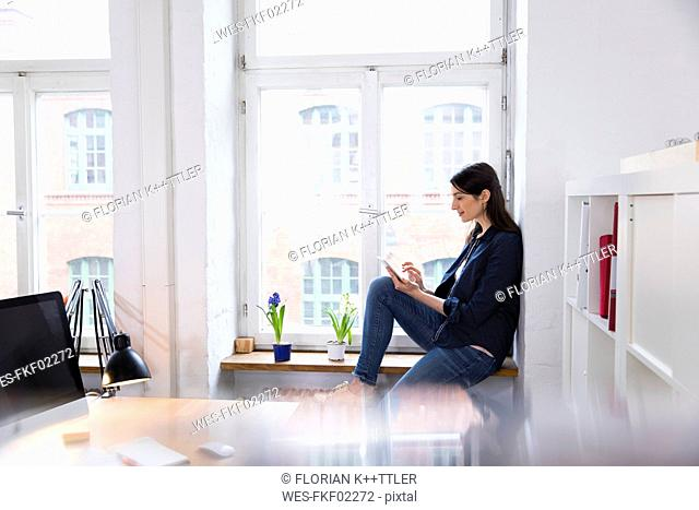 Woman using tablet at the window in office