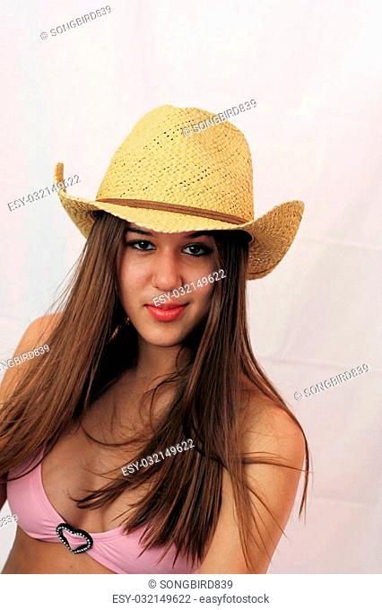 Pretty woman dressed in pink bikini and cowboy hat, ready for the Stampede