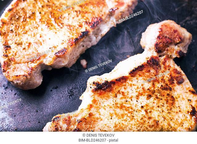 Pork chops searing in pan